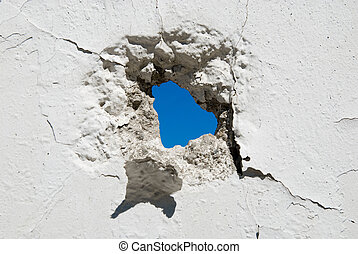 Concrete wall with holes . Crumbling wall of hostilities