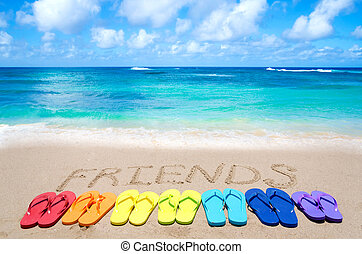 Sign quot;Friendsquot; and color flip flops on sandy beach -...