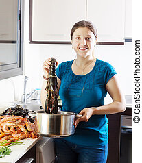 woman cooking with lobster in home