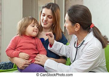 children's doctor looks throat of   baby