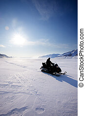 Snowmobile Silhouette - A snowmobile on frozen ice on a...