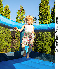 Girl in inflatable playground - Happy girl jumping on...