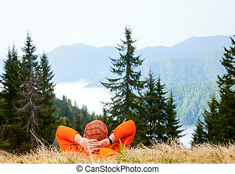 Hiker enjoying mountain view - Hiker resting at viewpoint...