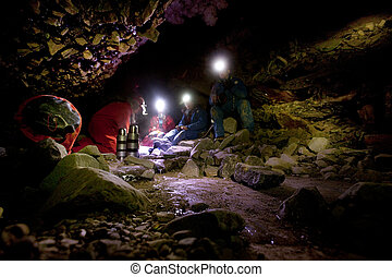 Cave Exporation - A group of people eating lunch in a dark...