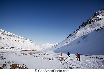 Svalbard - A group of people walking along a path ouside...