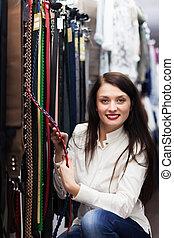 Girl choosing strap at shop