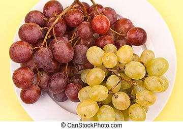 Green and blue grapes on plate isolated on yellow background