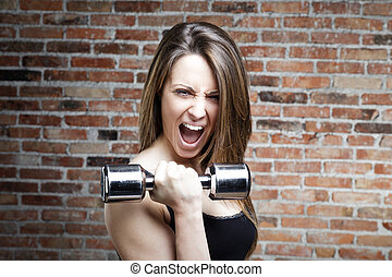 Young shouting fit woman lifting dumbbells