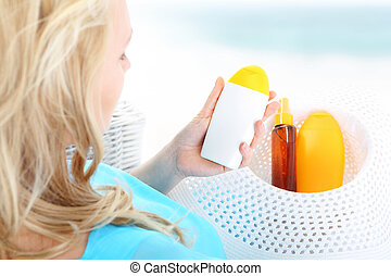 Tanning lotion - sunscreen . - A woman sitting in a basket...