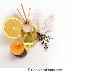 Yellow bottle with essential oil, candle on white