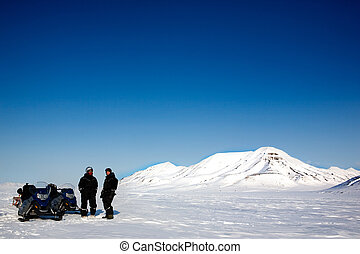 Snowmobile Tour - Two men on a snowmobile trip on Svalbard,...
