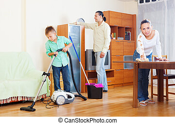 family of three with boy cleaning in room - Happy family of...