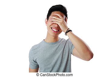 Portrait of a young man covering his eyes with his hand over...