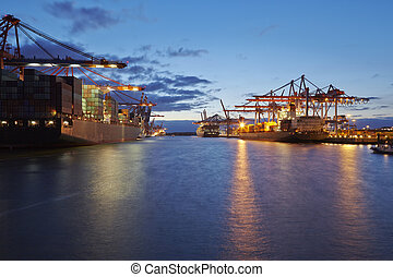 Container vessel at terminal in harbor in the evening -...
