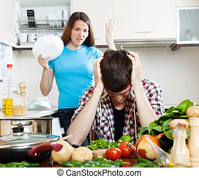 Sad man with angry wife at kitchen - Sad man with angry wife...