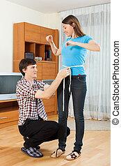 Guy measuring waist of girl