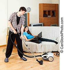 Man cleaning room during girl with notebook resting over...