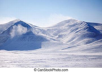 Snow Covered Mountain - A mountain with blowing snow in a...