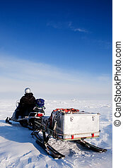 Man with Snowmobile - A man sitting on a snowmobile on a...