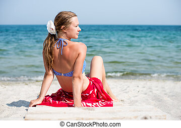 Woman sitting at the beach - Beautiful blonde woman sitting...
