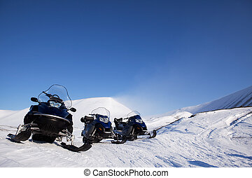 Snowmobile - Three snowmobiles on an outdoor winter...