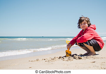 Boy playing in the sand on the beach in Cape Cod