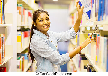 female indian college student pulling a book off shelf -...