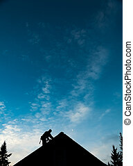 Contractor in Silhouette working on a Roof Top with blue Sky...
