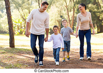 family walking in park - beautiful young family hand in hand...