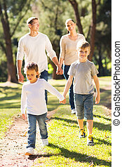 family walking together outdoors - happy family walking...