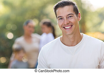 young man standing in front of family outdoors