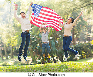 american family jumping with USA flag - cheerful american...