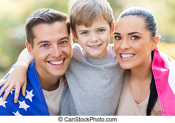lovely american family with US flag outdoors on 4th of July