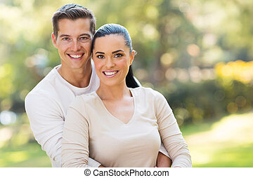 couple hugging outdoors - close up portrait of couple...