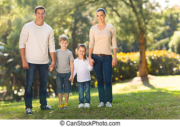 young family standing outdoors - portrait of young family...