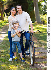 family of three outdoors - cute young family of three...