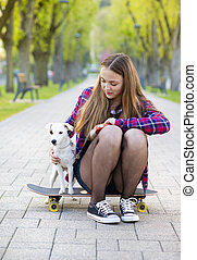 Teenage girl with skateboard and dog - Teenage girl on...
