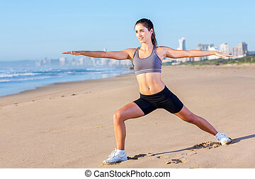 young fit woman stretching on beach - pretty young fit woman...