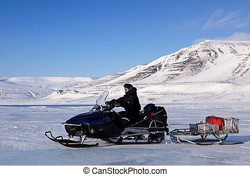 Snowmobile Expedition - A man on a snowmobile against a...