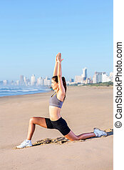 fit woman doing yoga exercise on beach