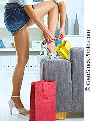 Long legs - Long female legs in stockings. Woman taking off...