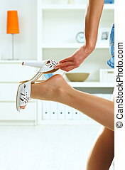 Woman taking off high heel shoe - Closeup photo of female...