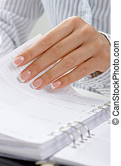Femal hand turning page - Closeup of female hand turning a...