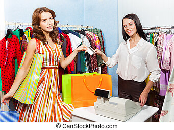 Happy woman paying with credit card for purchase - Happy...