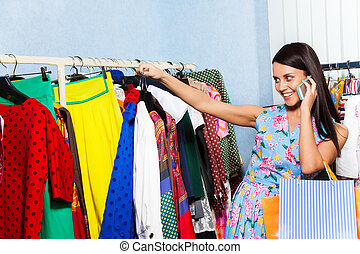 Young woman looking at chosen clothes with mobile - Young...