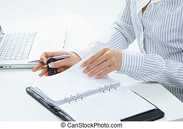 Femal hand turning page - Female hands holding pen and...
