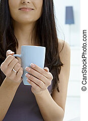 Woman holding tea cup - Partially visible young woman...