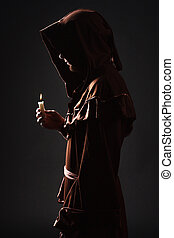mysterious Catholic monk - Mystery monk praying on kneels in...