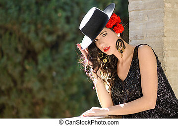 Woman wearing spanish hat and red carnations in her hair -...