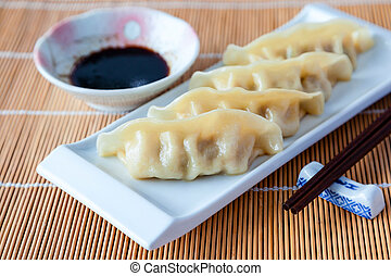 Delicious gyoza or pot stickers on bamboo mat - Gyoza or...